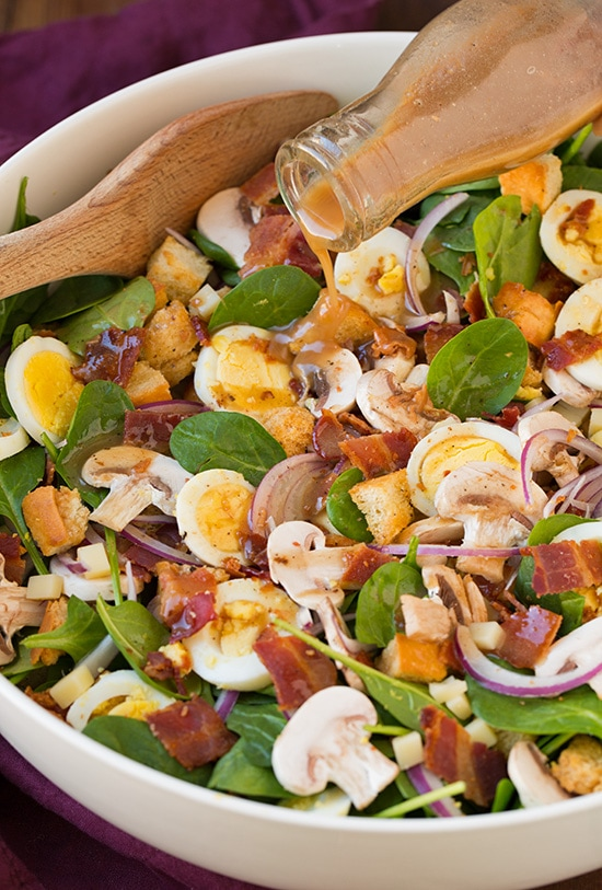 Spinach Salad with Warm Bacon Dressing in a white bowl
