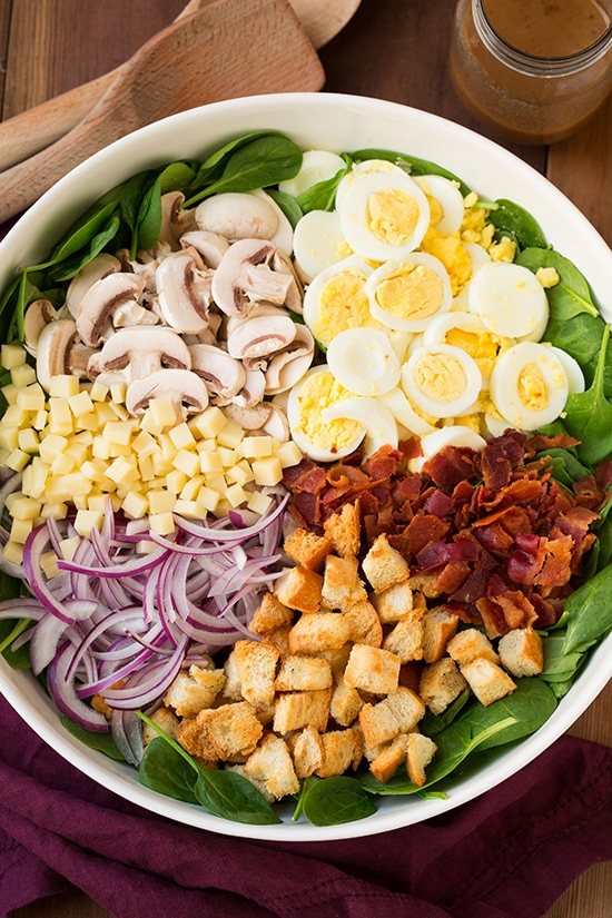 spinach salad with warm bacon dressing topped with cheese, eggs, mushrooms, bacon, croutons, and onions