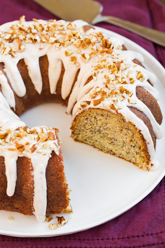 Banana Bundt Cake with cream cheese icing and chopped pecans with slice missing on white plate
