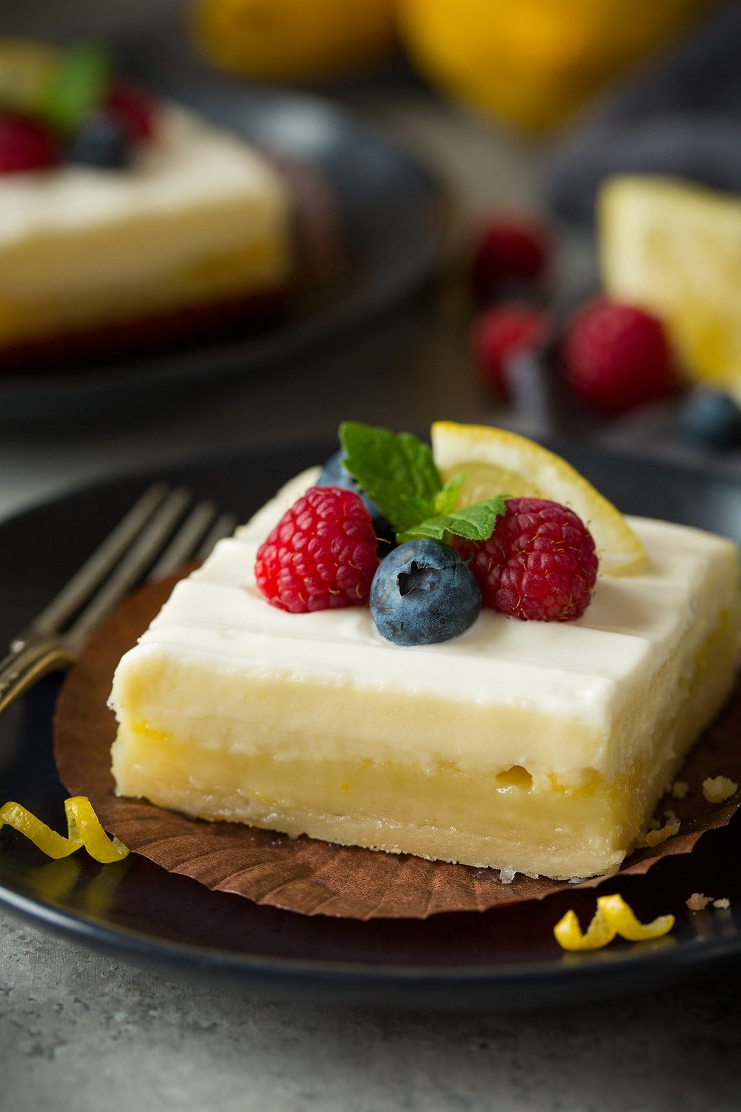 close up of Lemon Cheesecake Bar garnished with berries, lemon, and fresh mint