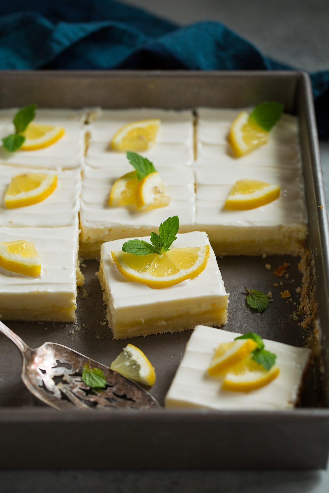 pan of lemon bars garnished simply with lemon wedges and fresh mint