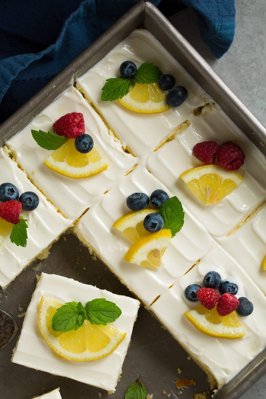pan of Lemon Cheesecake Bars, sliced and garnished with berries and lemon wedges
