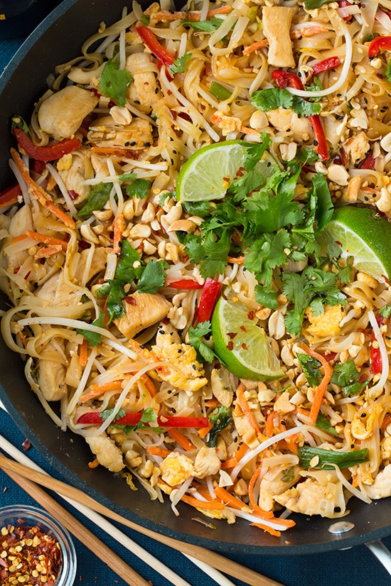 A close up of Chicken Pad Thai in a pan with lime wedges