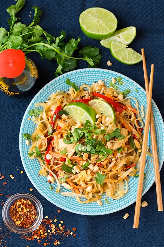 An overhead shot of chicken Pad Thai on a blue plate with chopsticks and lime wedges at the side