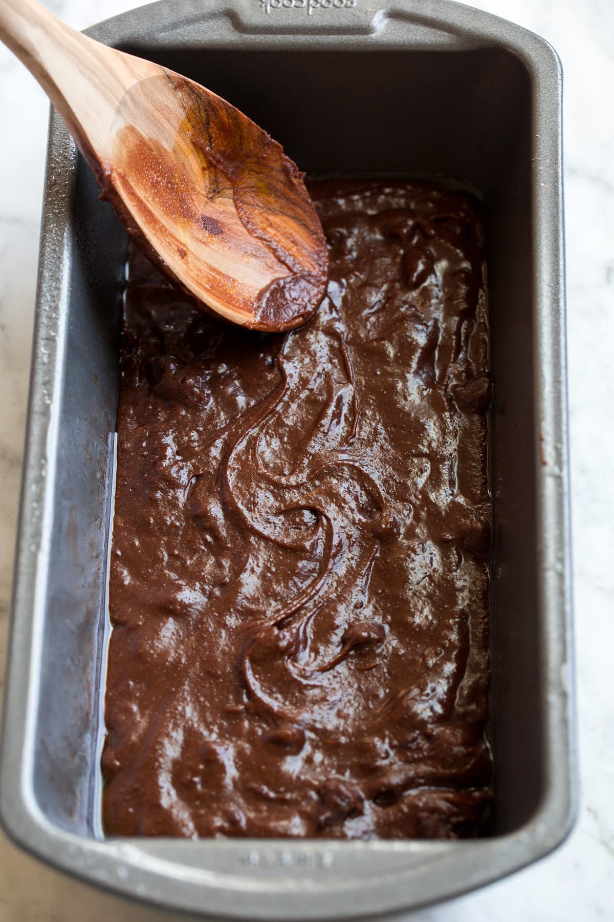 Brownie batter being spread into a bread pan.