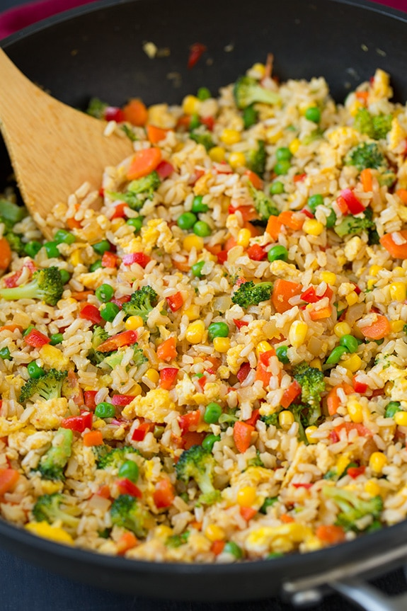 veg fried rice in a skillet with a wooden spoon