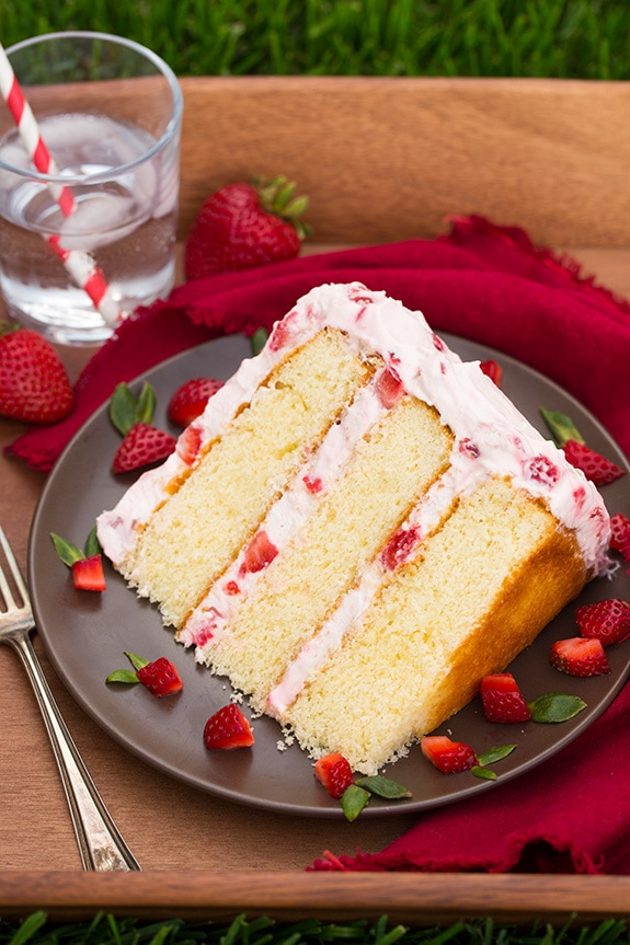 Fresh Strawberry Cake slice on a plate with cut up strawberries