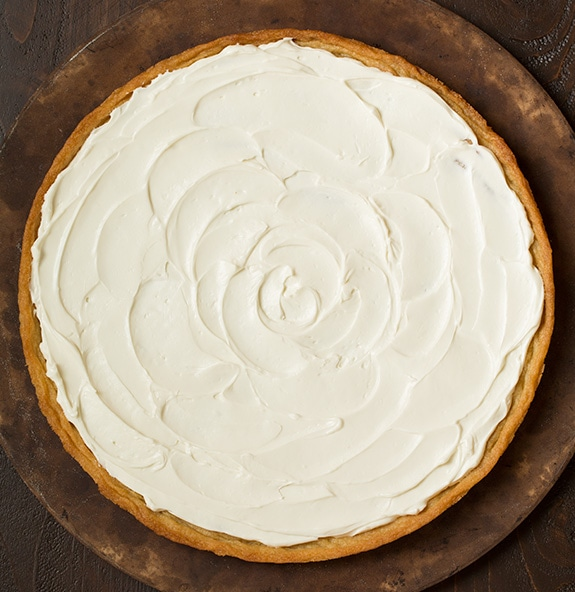 Spreading layer of cream cheese frosting over cookie crust.