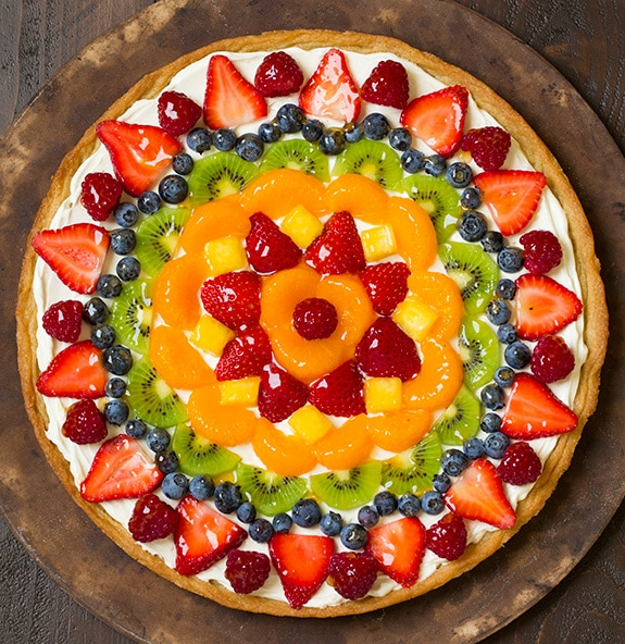 Adding fruit and jam to fruit pizza.