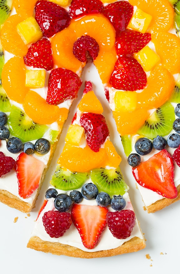 Fruit pizza with one slice cut.