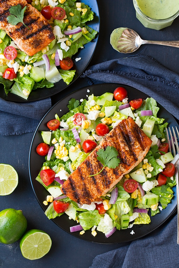 two plates of mexican grilled salmon salad drizzled with avocado ranch dressing