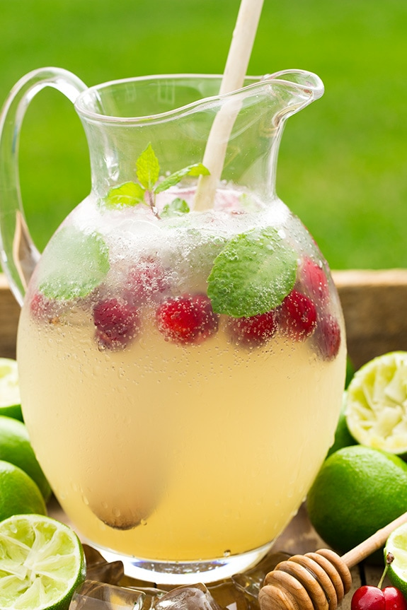 homemade Limeade in glass pitcher with mint and raspberries