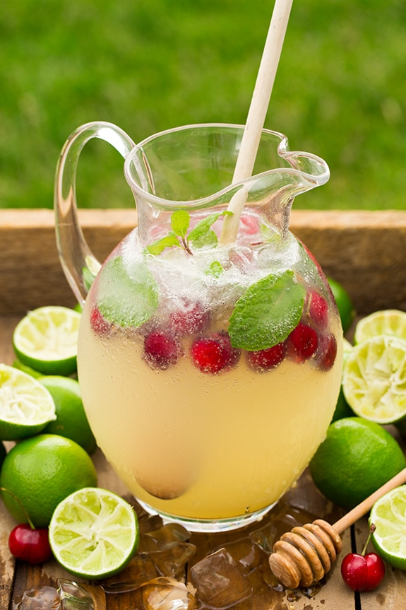 limeade in glass pitcher with raspberries and mint leaves, on tray with limes