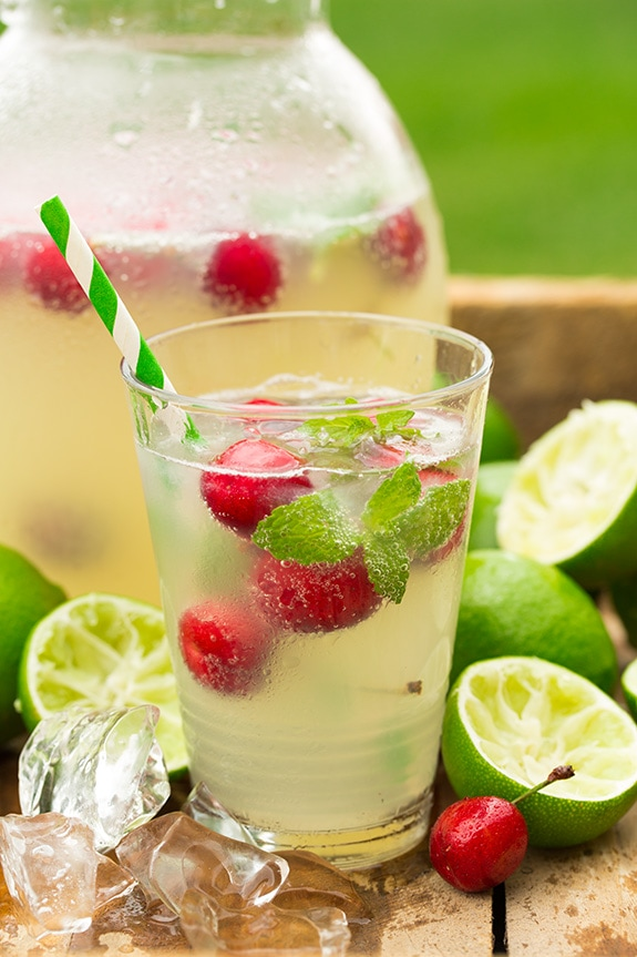 Glass of ice cold limeade with raspberries, mint, and honey