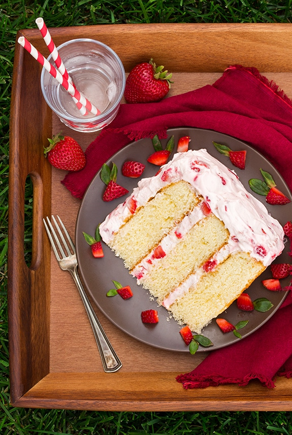 slice of Fresh Strawberry Cake on a plate with a fork and glass