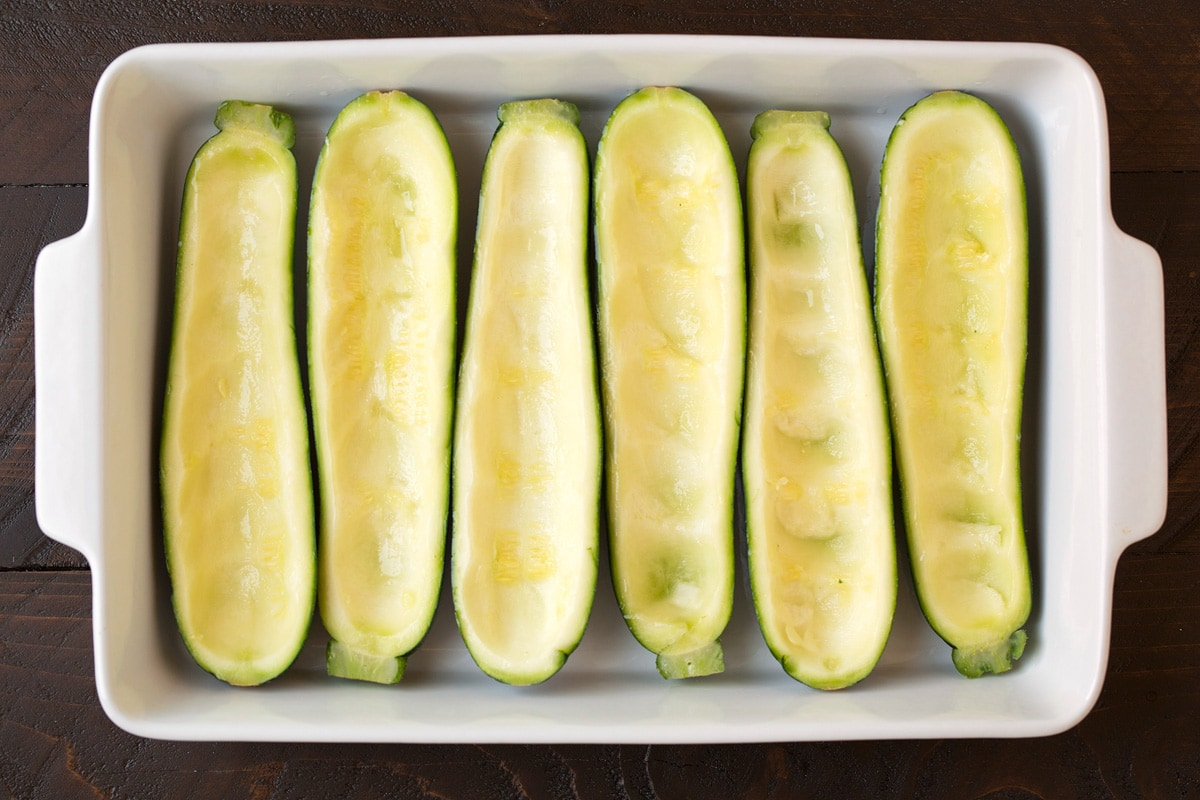 Hollowed out zucchini made into boats in a baking dish before adding filling.