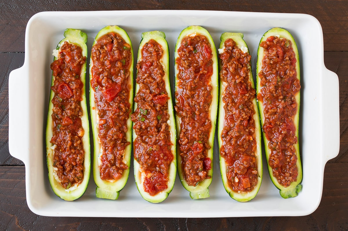 Adding sauce layer to zucchini boats.