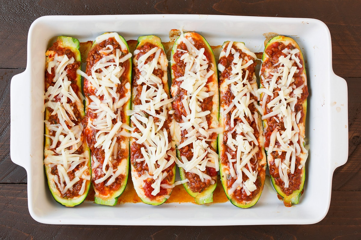 Adding shredded cheese over sauce layer in zucchini boats.