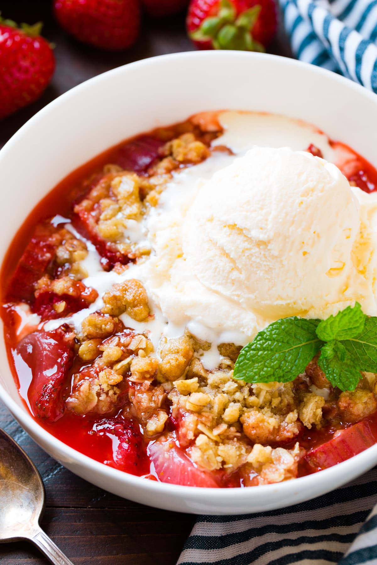 Strawberry Rhubarb Crisp in a single serving bowl topped with vanilla ice cream.