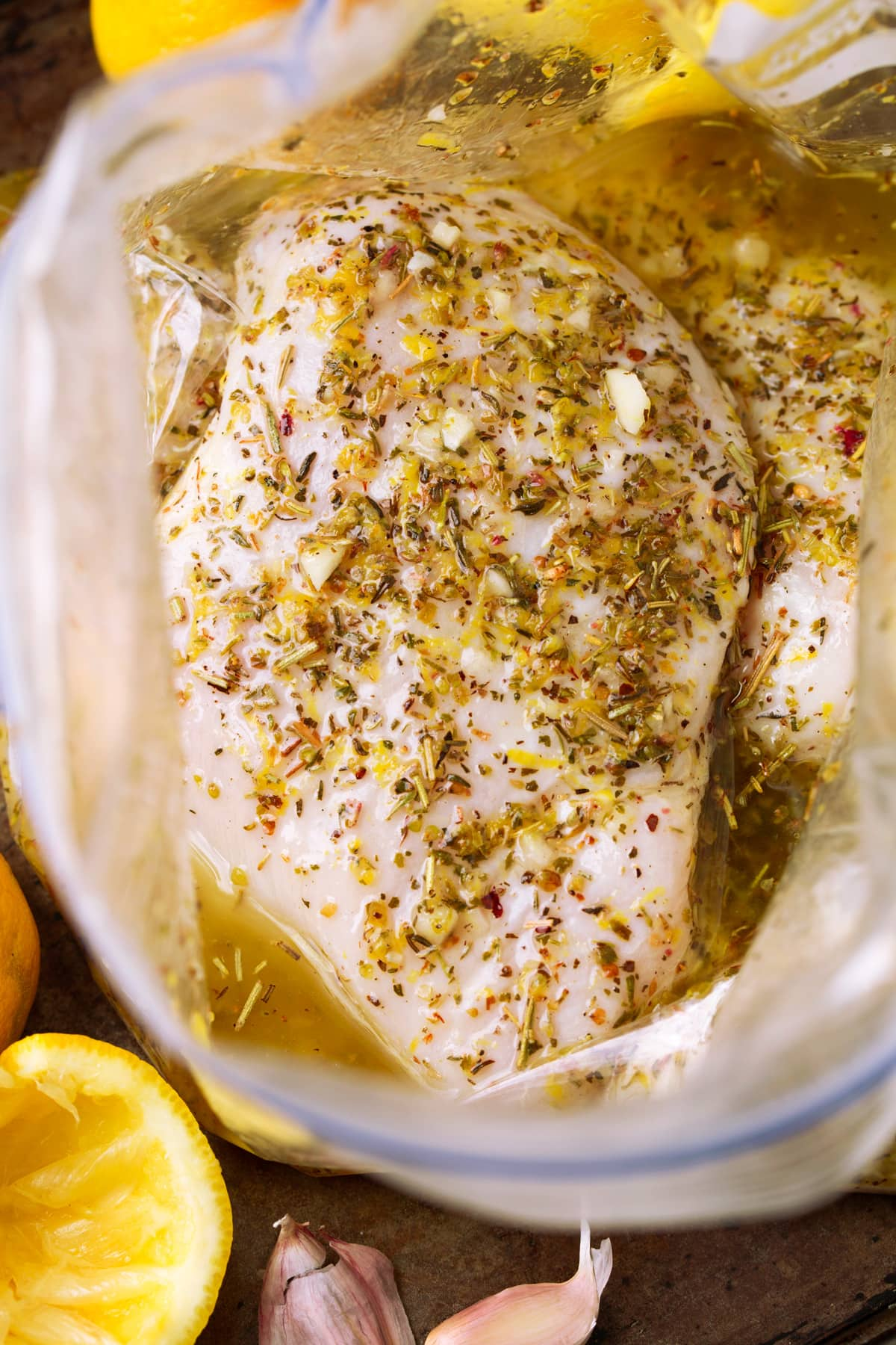 Greek lemon chicken soaking in marinade in a bag.