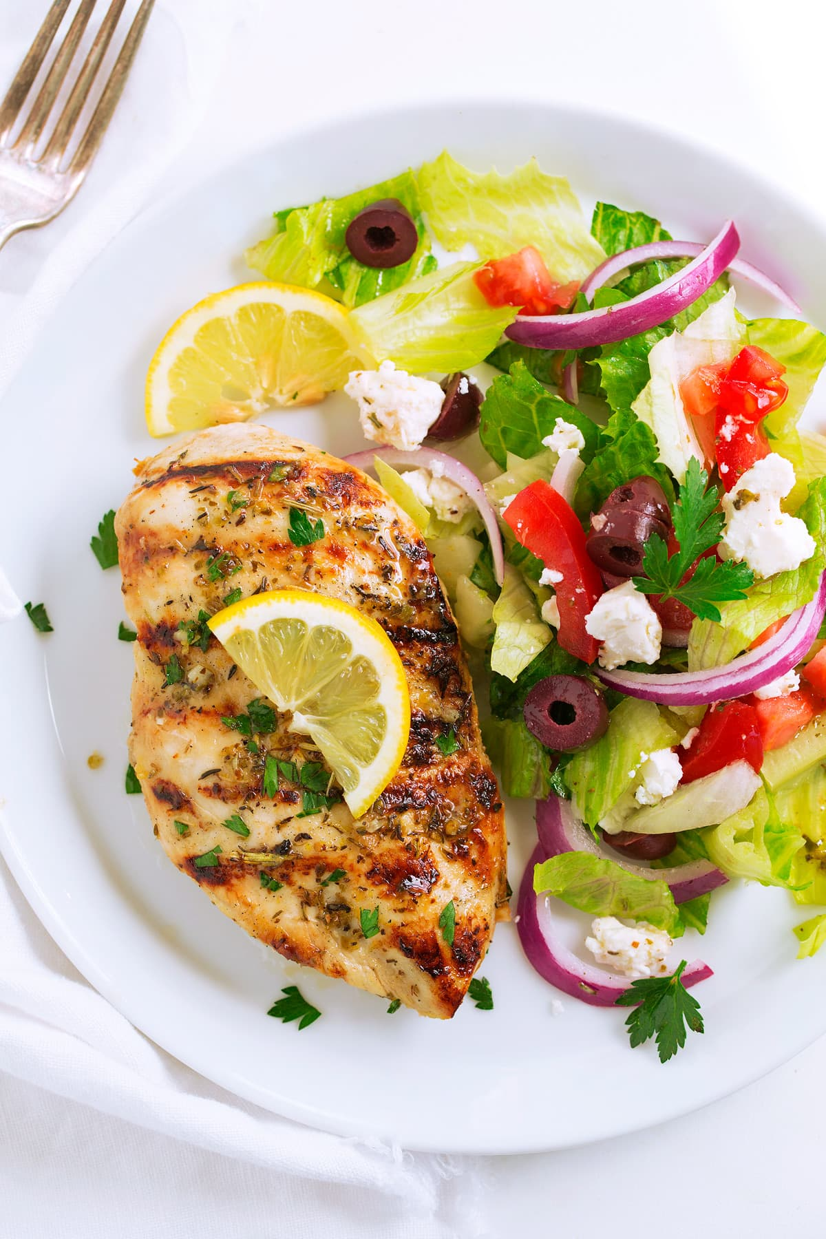 Greek lemon chicken with a side salad on a serving plate.