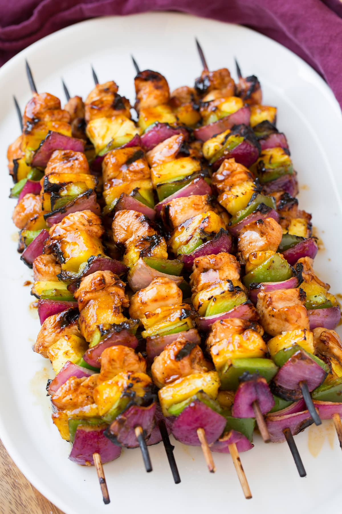Marinated hawaiian chicken skewers on a white serving plate.