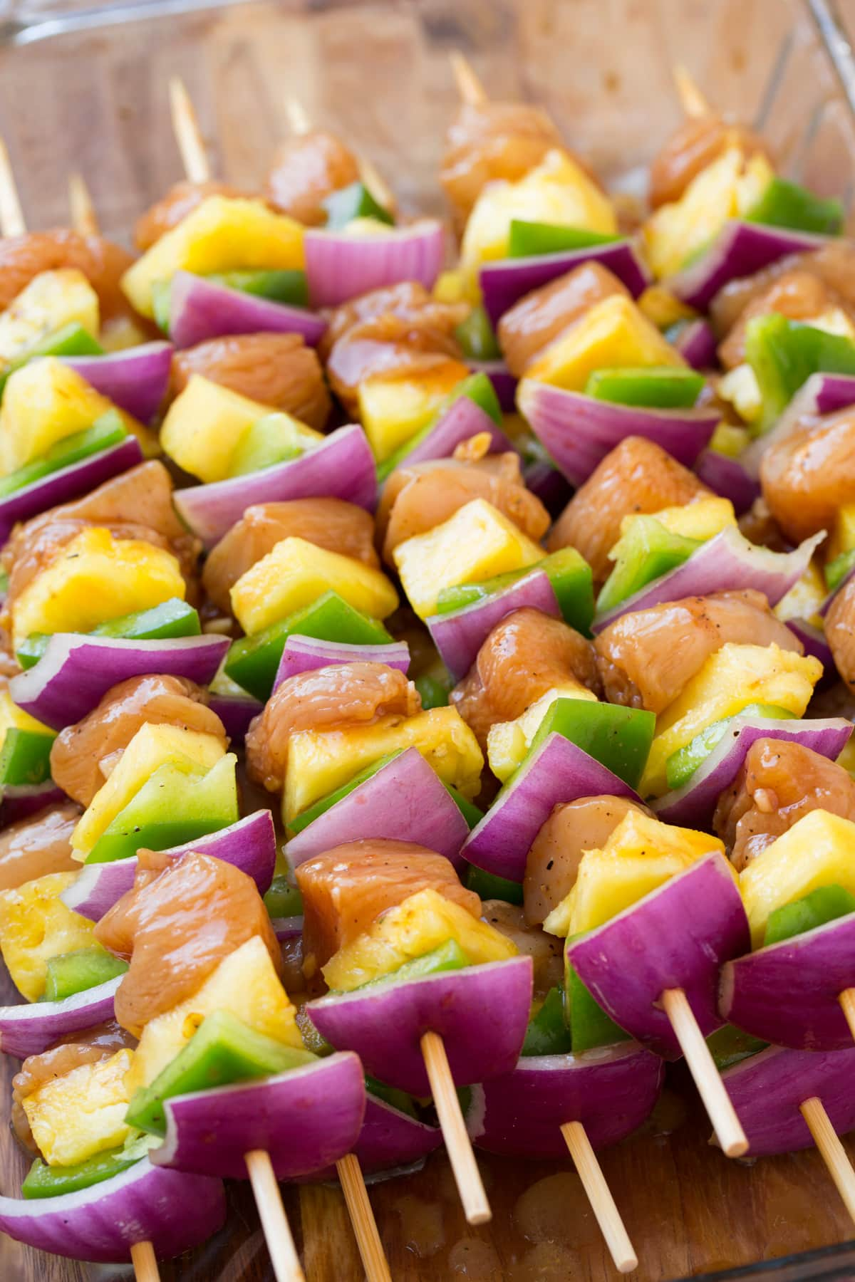 Chicken skewers with bell pepper red onion and pineapple. Shown before cooking.