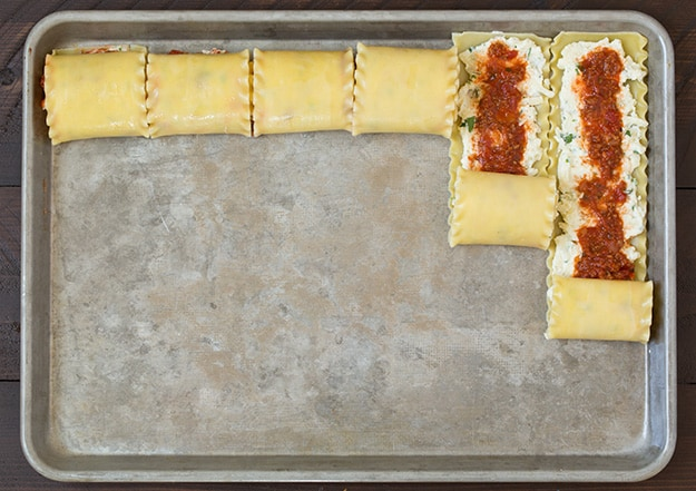 Lasagna Roll Ups on a baking tray getting rolled up