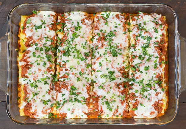 Lasagna Roll Ups out of the oven with melted cheese and basil
