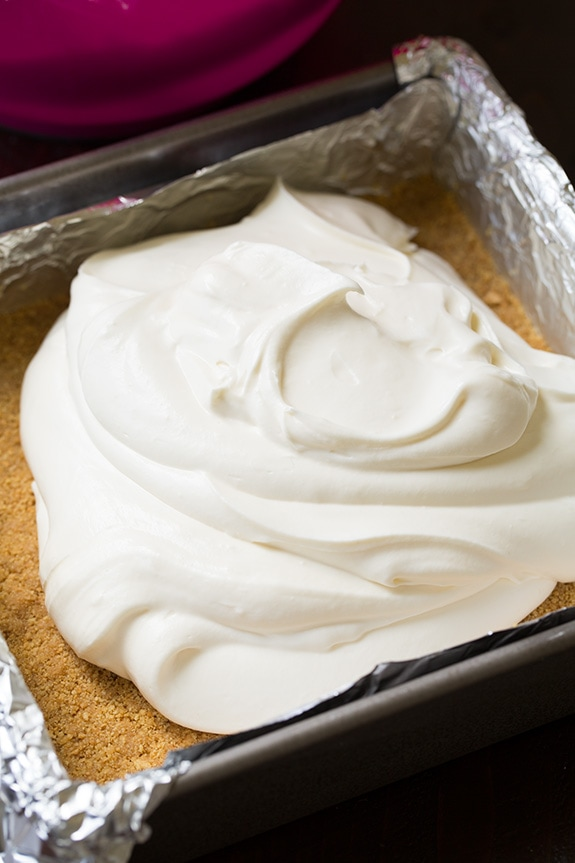 Showing how to make no bake cheesecake. Spreading cream cheese filling over graham cracker crust in baking dish.