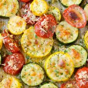 A close up of roasted zucchini and other veg on a roasting pan