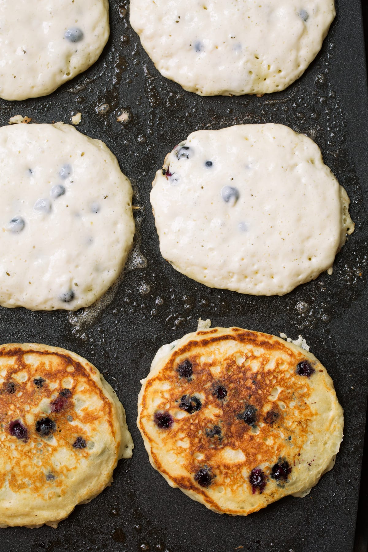 Showing how to cook blueberry pancakes on a griddle.