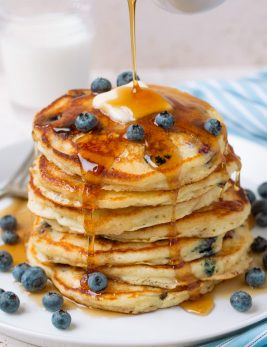 Pouring syrup over stack of homemade blueberry pancakes