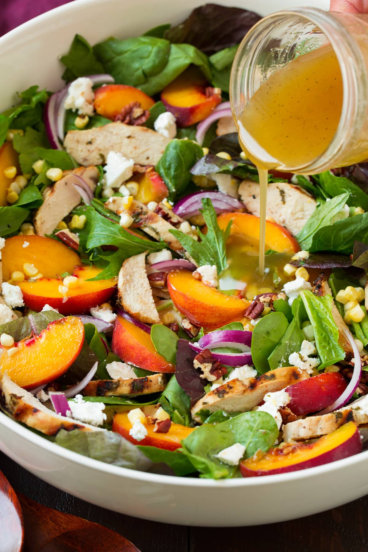Pouring dressing over peach salad.