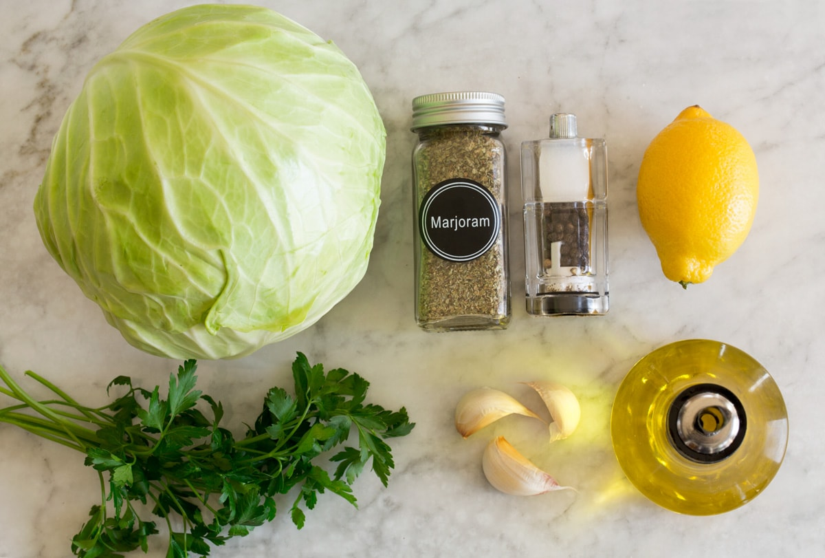 Photo: Ingredients used in making roasted cabbage are shown here. Includes fresh cabbage, olive oil, garlic, parsley, lemon, salt, pepper, and marjarom.