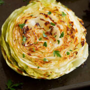Photo: A roasted cabbage slice is shown from close up. It is golden brown and garnished with parsley.