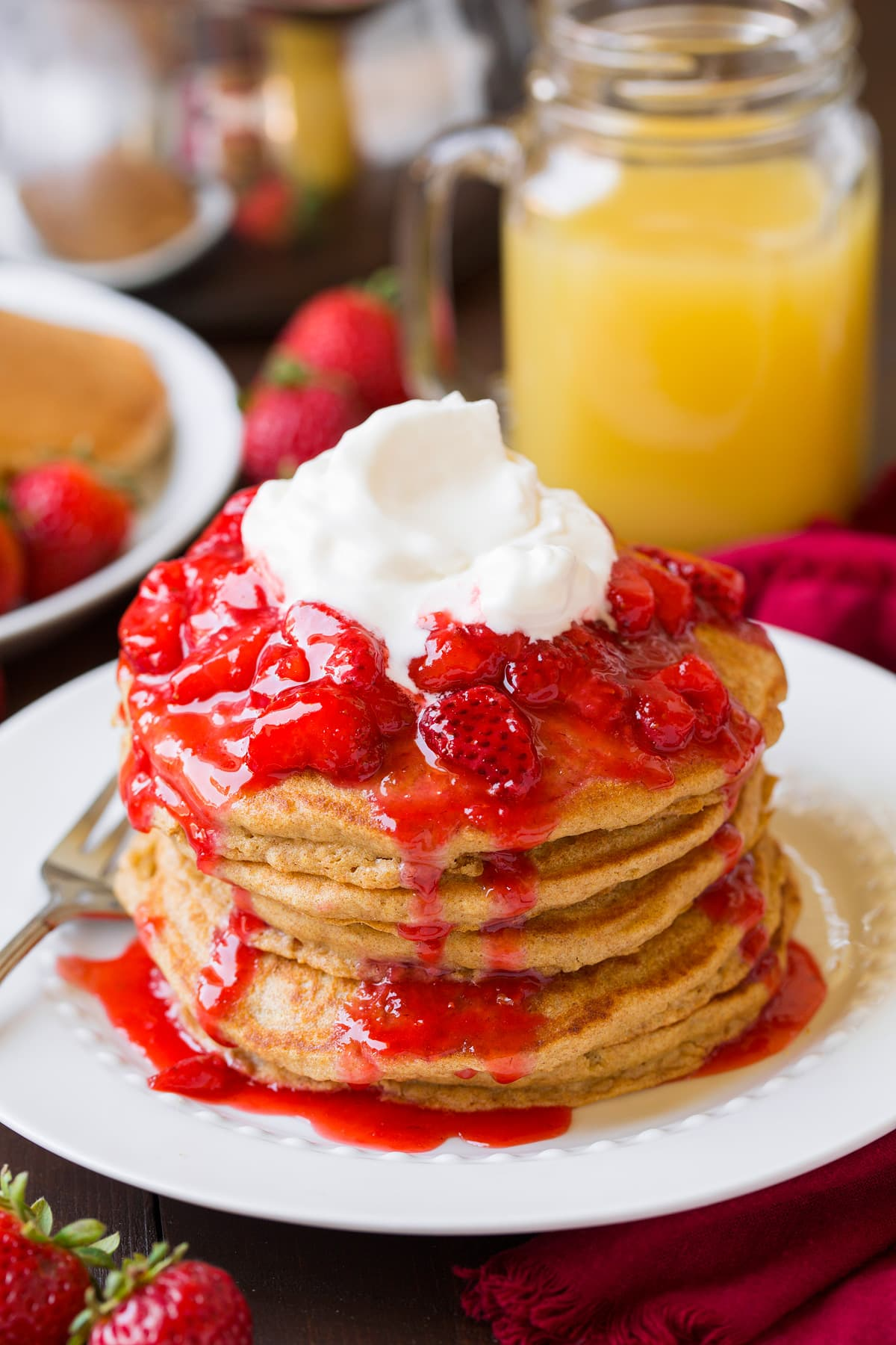 Whole Wheat Pancakes topped with strawberry syrup and whipped cream.