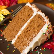 Layered spice cake with cream cheese frosting on a matte brown plate decorated with fall colored sprinkles.