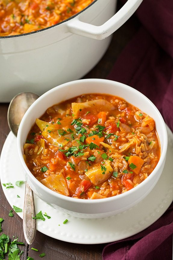Serving of cabbage roll soup shown in a white bowl sitting on a small white plate.