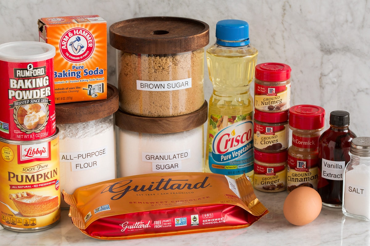 Image of ingredients used to make pumpkin chocolate chip cookies. Includes flour, white sugar, brown sugar, egg, spices, vanilla, chocolate chips, vanilla, baking powder, baking soda and pumpkin.