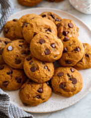 Image of pumpkin chocolate chip cookies stacked on a white serving plate.