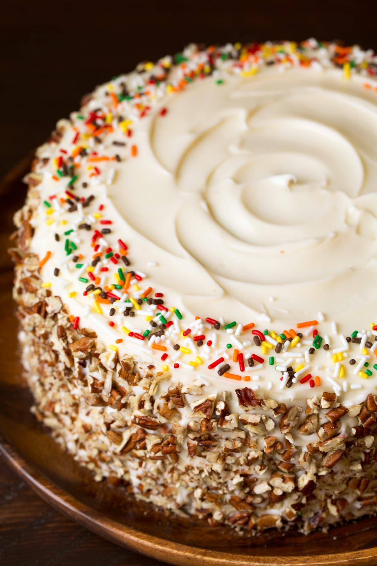 A whole round spice cake without any slices cut. It's covered with a cream cheese frosting, chopped pecans around the edges and fall sprinkles around the top.