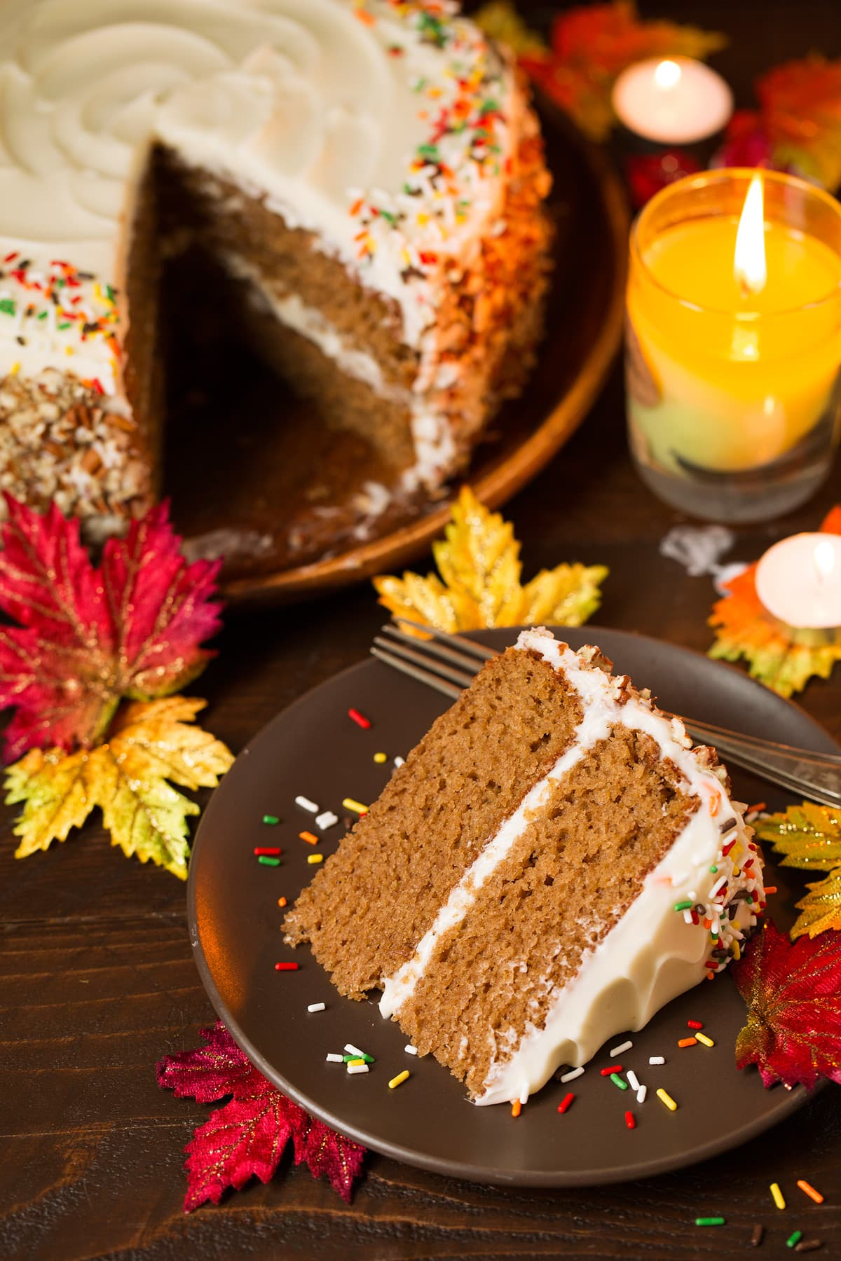 One slice of spice cake on a single serve plate and a whole spice cake is in the background. Decorations in the image include fall leaves, a lit candle and a wooden surface.