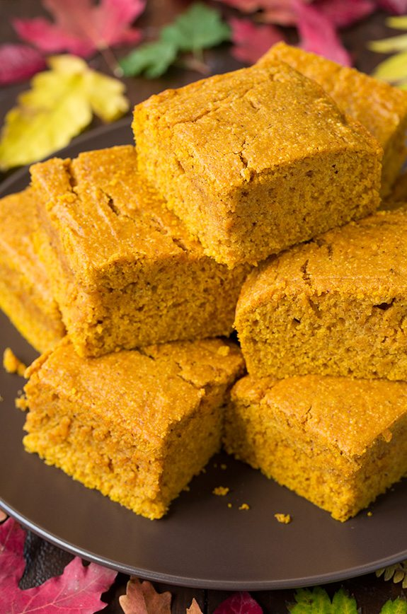 Close up image of Pumpkin Cornbread slices staked on a dark brown plate.