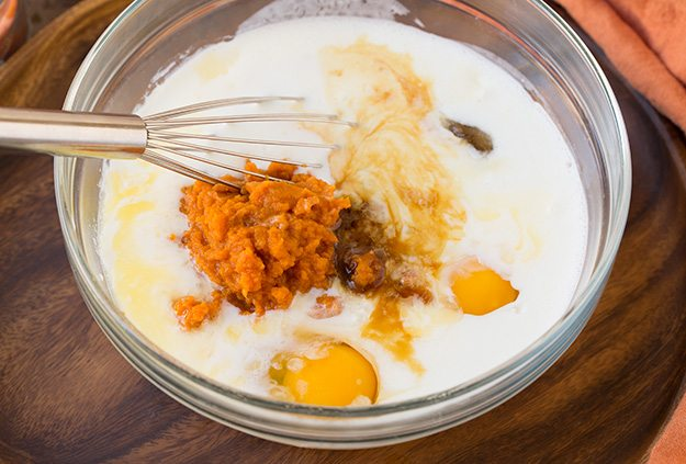 Mixing eggs, pumpkin, buttermilk, and sugar in a glass mixing bowl.