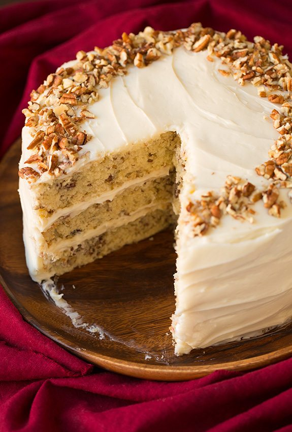 Butter Pecan Cake on a wooden platter. A large slice is removed from cake to show interior.