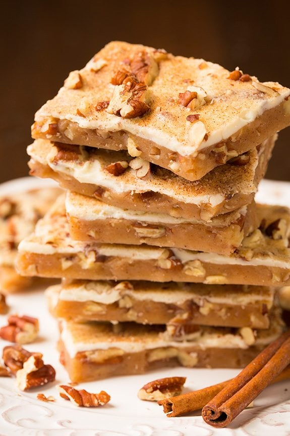 Stack of toffee with white chocolate and pecans on a white plate.