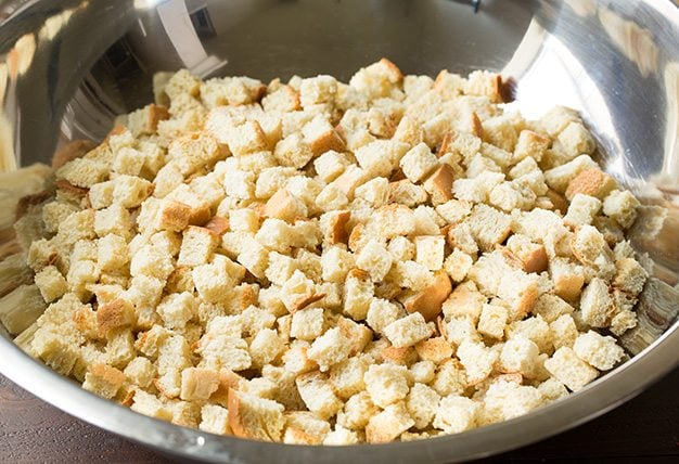 Dry bread cubes in extra large mixing bowl, first step to make stuffing.