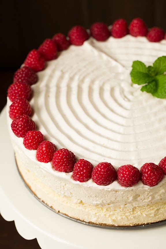 Image of a whole cheesecake decorated with swirled whipped cream on top, fresh raspberries and mint.
