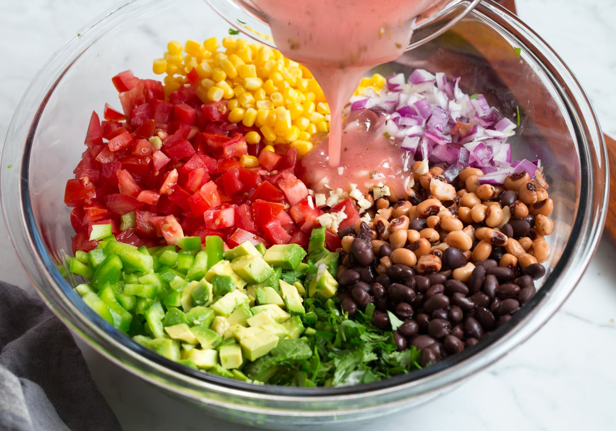 Cowboy Caviar adding dressing to veggies and beans in mixing bowl
